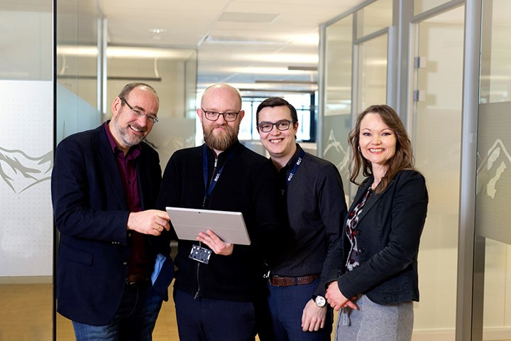 Four employees at ECIT within accounting, business solutions and IT are solving a customer's needs in the hallway together.
