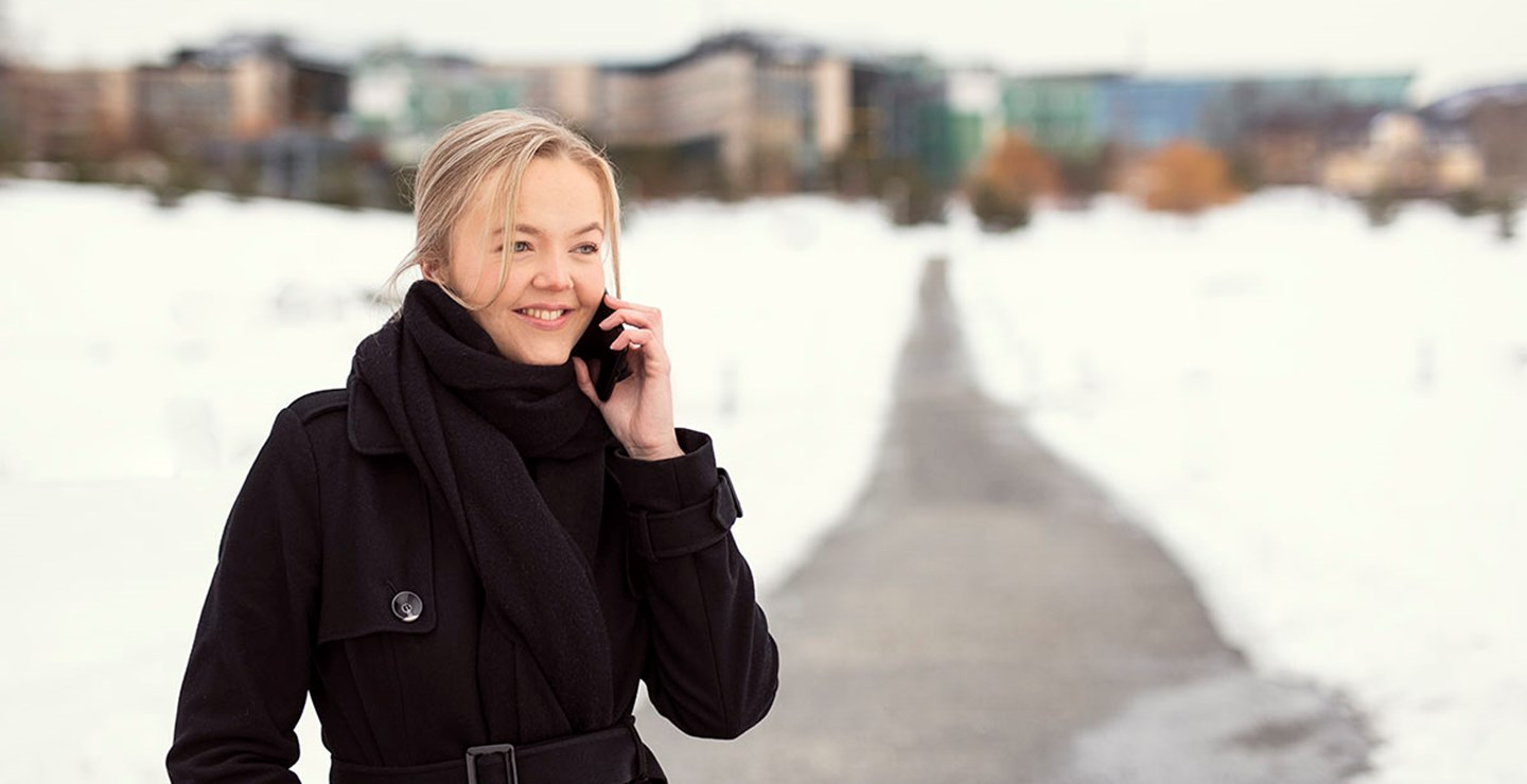A young woman employed at ECIT speaking on the phone outside at Fornebu, Norway.