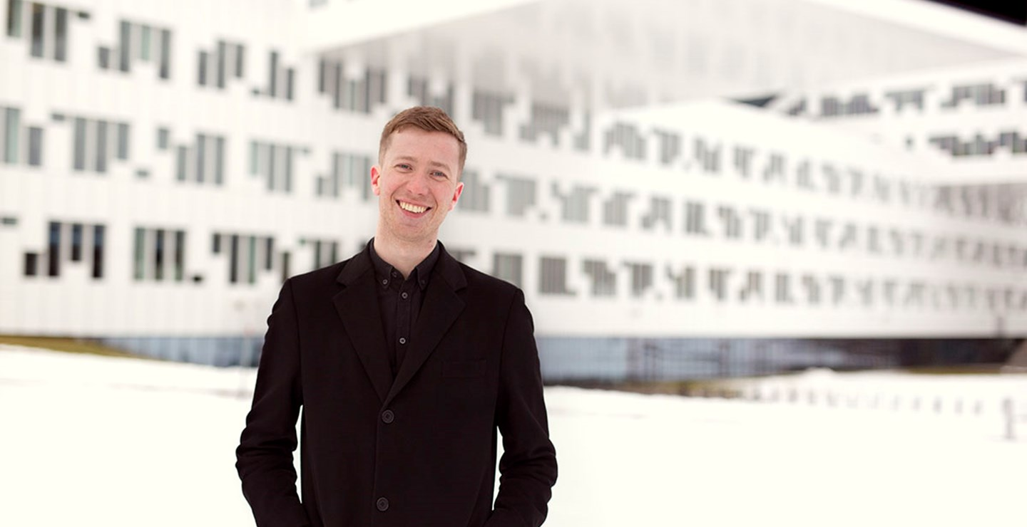 A young man employed by ECIT is standing in front of an architectural building at Fornebu, Norway.
